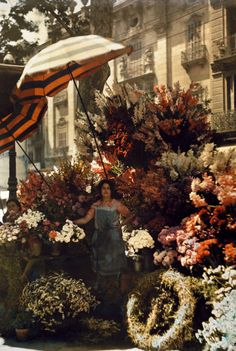 A woman stands in front of her flower stand on the Rambla in Barcelona, Spain, March 1929 (autochrome). By Jules Gervais Courtellemont, National Geographic