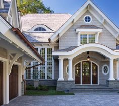 LOVE LOVE LOVE. Love the door, the curved porch roof, the additional cover over the garage doors, the garage doors, the colors and the siding with stone. Also really digging the copper gutters and the stone paver driveway