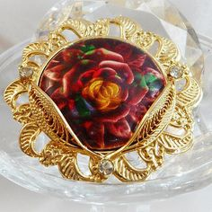 This #vintage rose under glass brooch is incredible.  This fabulous work of art is very unique.  It consists of a colorful pink, red, green & gold cabbage rose under a domed... #ecochic #etsy #jewelry #jewellery #holiday2014etfs