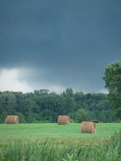 Hay bales in a green field under a summer storm. Michigan.