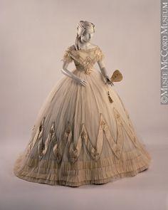 Dress About 1860-1863, 19th century Fibre: silk (net, taffeta, lace, ribbon); glass (simulated pearls); Sewn