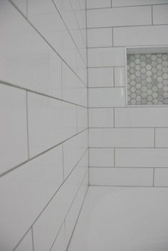 Choosing our shower tile design with subway tile and marble tile niche. This white and gray bathroom features IKEA vanities and herringbone floor. Tile Shower Niche, White Subway Tile Shower, Beveled Subway Tile, Marble Tile Bathroom, Subway Tile Showers, Shower Tile Designs, Marble Showers, Diy Bathroom Vanity, Bathroom Floor Tiles