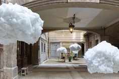 visitors are invited to place their heads within open areas of the oversized white puffs, reflecting on the dark and private space around them.