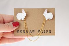 These lovely little rabbit collar clips have been carefully hand drawn, cut, and coloured at my home studio in Hertfordshire, England. They look