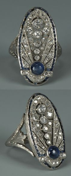 An Art Deco 18k white gold, diamond and sapphire ring. In the shape of a closed dragonfly with one bezel set round cabochon sapphire and five descending round bezel set diamonds surrounded by pave set diamonds and outlined by 44 bezel-set baguette sapphires weighing approximately 1.00 carat. Total weight of 46 diamonds approximately 2.00 carats.