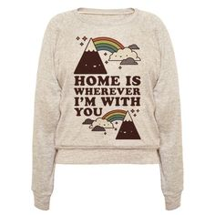 """Show that homes not a place, it's a person, with this super cute shirt. This design features an illustration of a happy little mountain and happy little cloud being connected by a rainbow along with the phrase """"Home is Wherever I'm With You."""""""
