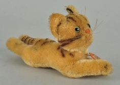 This cat does not appear in any of the standard Steiff reference books and was probably produced for the upscale US toy retailer F.A.O. Schwarz.  Cat is 7 cm tall and 17 cm long, including her outstretched tail.  She is lying, head jointed, and made from tan mohair that has darkened over time.  She has black airbrushed stripes on her head, back, and tail.  She is hard-stuffed with excelsior. Her face is detailed with green and black slit pupil eyes, a pink hand embroidered nose and mouth…