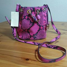 NWT Mk Snakeskin Crossbody Truly beautiful snakeskin hot pink and black crossbody with gold hardware. NWT. GORGEOUS. My daughter lost her mind when she saw this so a trade is going to have to something spectacular for me take on her wrath and unlike my others there's a timeclock on this. It is small. 9 inches across, 6.5 inches down and shoulder strap extends 21 inches. Trade value is $300 Michael Kors Bags Crossbody Bags