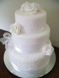Here's an idea - lace around the cake. Perhaps better in ivory to match the dress?