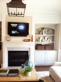 TV over the fireplace with built-ins and demijohn on coffee table