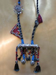 Kinship Stories: Tribal art necklace whose base is made with Indian fabric, using a traditional Turkish technique. The mixed silver piece is a vintage Yemeni amulet. Dangling from the amulet are vintage Uzbek tassels that come from old tapestry. The triangles are Afghani and are also used as amulets. On the other side is a brass Turkoman nose ring. It is a rare piece of museum quality. The button is Nepali and made of Yak horns. The necklace is entirely handmade and one-of-a-kind.