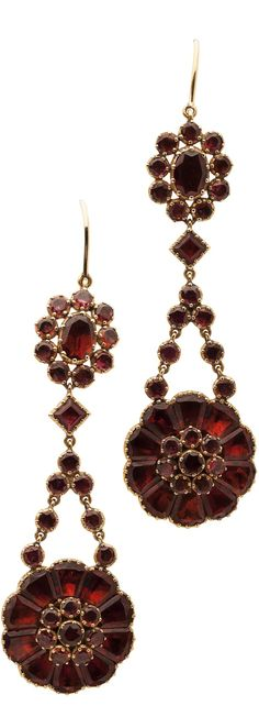 A pair of garnet set pendant earrings, each composed of two foil backed garnet clusters with similarly set conjoining links, set in unmarked yellow metal with hook fittings, Length: 65mm