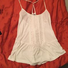 SaleWhite American Eagle peplum top White American Eagle peplum top with embroidered appliqué down the front. Faux Suede straps. Fits loosely American Eagle Outfitters Tops Tank Tops