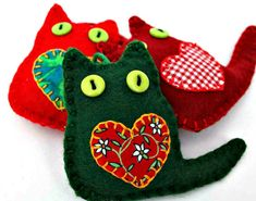 Set of three colourful cat Christmas ornaments. Little felt cats with appliqued fabric heart and button eyes. They are lightly padded, with