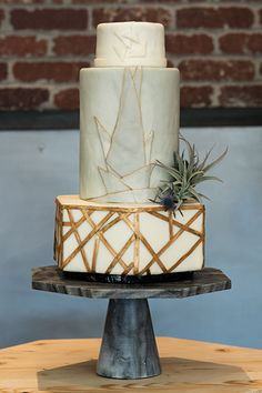 This non-traditional cake is all about the shapes. Round and hexagonal silhouettes contrast with one other while various geometric designs play together for an urban artsy vibe.