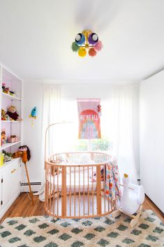White walls mixed with pastel accents and a mid century modern inspired cribe and rainbow flushmount ceiling wall fixture. Flush Mount Kitchen Lighting, Sconce Lighting, Baby Girl Nursery Decor, Nursery Design, Nursery Lighting, Ceiling Fixtures, Ceiling Lights, Modern Lighting Design, Rainbow Decorations
