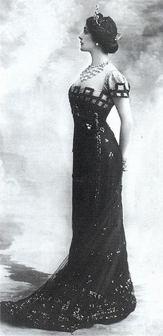 Statuesque grace personified in a beatiful figure hugging gown. 1910