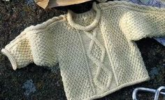Un pull moelleux et décontracté à tricoter pour bébé : il décline point de blé, losanges et torsades : Tailles : 6 - 12 et 24 mois Aiguilles N° 3,5 et 4,5 La marinière et le bonnet Le pull irlandais en lambswool