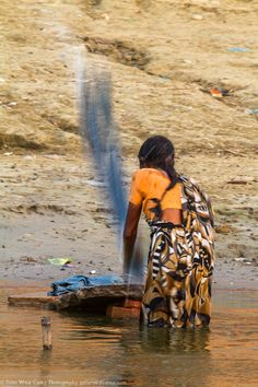 Morning Wash - A woman does laundry by pounding out water on stones along the Ganges River in Varanasi, India.