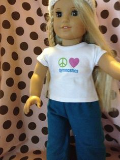 """Peace, Love, Gymnastics t-shirt and pajama pants made to fit 18 inch dolls. Shirt is white with green peace sign, pink heart and blue gymnastics. Pajama pants are a dark teal blue that matches the """"gymnastics"""" on the shirt. Great for the new McKenna who loves gymnastics."""