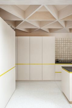 A glulam (glued laminated timber) beam frames the ceiling over the kitchen; the ceiling is made up of a prefabricated triangular plywood module braced by plywood skin, acting as the floor for the upper storey.
