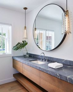 Contemporary bathroom features hanging pendants, round mirror, and floating vanity, countertop is Honed Barroca Soapstone.