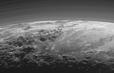 Pluto - Norgay Montes (left foreground); Hillary Montes (skyline); Sputnik Planitia (right). Near-sunset view includes several layers of atmospheric haze.