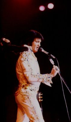 Elvis on stage at the Las Vegas Hilton in september 1973 , here the closing show of his summer season shows at the Hilton. Here playing with a toy monkey.