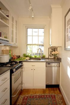 Tiny kitchen. L-shaped. Stainless appliances. Herb window box with sash windows. Gas stove. White cabinets. Single sink.