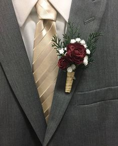 Beautiful boutonnieres made with silk and faux evergreen sprigs and dark red maroon burgundy flowers, accented with babys breath and wrapped in gold ribbon. Each is about 4-5 in height. Perfect for Groom, Groomsmen, Ring Bearer, Father or Mother of the Bride and Groom! Flower