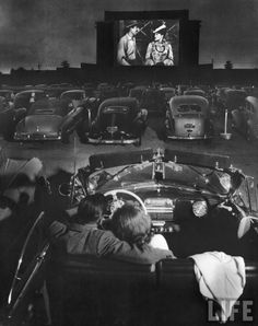 Watching Movies in 40's Pic 1 : Drive In movie, rear view of young couple snuggling behind the wheel of his convertible at a drive-in movie .../ vintage / photography