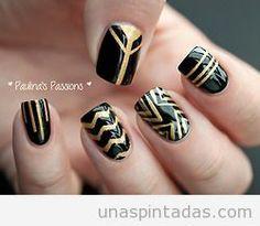 Decoración de uñas en negro y dorado con estampados metálicos