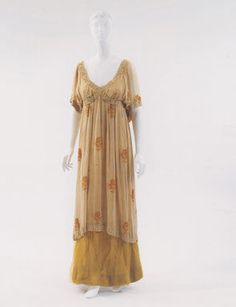 Evening gown worn by Isadora Duncan, designed by Paul Poiret, Paris, ca. 1912. Cream cloth tunic-style gown with chenille-like design of gold roses.