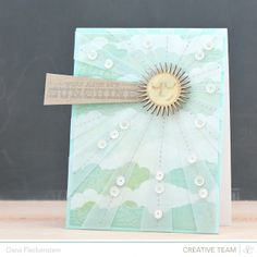 handmade sunburst ... card by @pixnglue ... background paper of soft aquas with clouds ... sun bursting with vellum rays machine sewn down with silver thread ... irrisdescent sequins strewn along the ray lines ... delightful card! ... Studio Calico