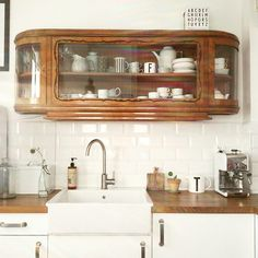 The simple white kitchen really highlights this gorgeous vintage cabinet. The wooden work surface ties the two together.