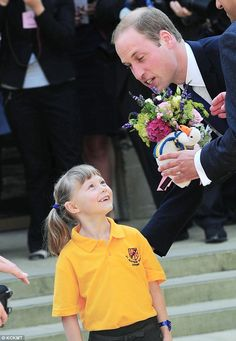 Thanks: The prince put his arm round Bethlily Barton, five, from St Aloysius School in Oxford, presented William with a toy swan for Prince George