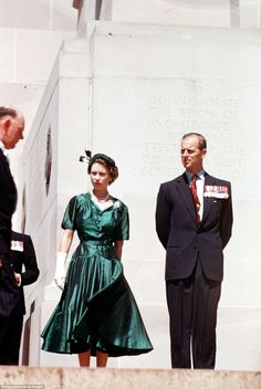 Queen Elizabeth dressed in green satin is pictured with the Duke of Edinburgh in 1954 stan...