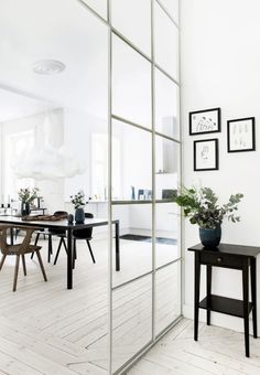 Dining room interior design with a glass (door?) divider. Ikea black nightstand