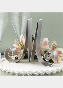 """Add a personal touch to the top of any cake with a lightweight, silver-tone initial cake top. Or combine initials using the ampersand design.   Cake Tops stand about 5"""" tall, measure about 6 .5"""" across and are 1"""" deep.  View LettersNote: Only the following letters are available for purchase: A, B, C, D, G, H, J, K, L, M, N, P, R, S, T, W, and the Ampersand Sign."""