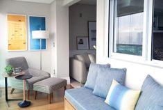 Varanda no mesmo nível da sala, poltrona com apoio de pés, mesas, iluminação embutida e abajur de piso, quadros pendurados na parede. Sofá com futon e amofadas. Piso de madeira, cortina na varanda. Varanda decorada, decoração. Reforma e decoracao apto completo