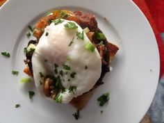 A Scottish breakfast stack. Potato scone, Lorne sausage, black pudding, poached egg, mushrooms and parsley.