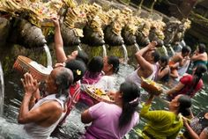 TIRTA EMPUL, INDONESIA - people pray and bath themselves in the sacred waters of the fountains, in Tirta Empul, Bali, Indonesia