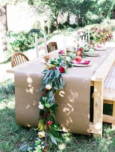 A butcher paper table runner and mismatched vintage chairs make for an informal yet elegant design, without breaking the bank. Via Style Me Pretty