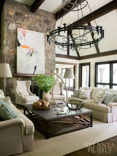 "This room proves that you don't have to pick a ""style."" Traditional, laid-back furnishings pair perfectly with modern art and a rustic fireplace."