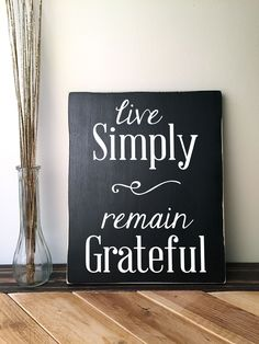 Handmade wooden sign with quote: Live Simply Remain Grateful