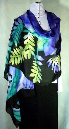 A beautiful soft silk to wrap yourself in any time of the year. Just the thing to go over your shoulders in warmer climates or to use as a scarf over a coat to bring color to winter days and nights. I have hand painted this silk in soft colors of teal, chartreuse and purple with a deep black background. The silk is a lightweight charmeuse that reflects the light beautifully. Measurements are 74 inches long and 23 inches wide with black chiffon 2 inch borders on each end. Can be hand washed…