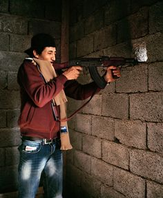 Magnum Photos -  Tim Hetherington LIBYA. Misurata. April 18, 2011. Ahmed, a young rebel fighter from Misrata, fires on Gaddafi loyalist positions from an abandoned and incomplete residential building. This firing position was three floors up, overlooking Tripoli Street with a clear view of the battle lines in the city.