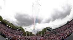 Queen watches military fly-past as thousands cheer