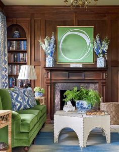 Gorgeous wood paneled den features a green velvet roll arm sofa on caster legs flanked by windows dressed in white and blue curtains facing a burlap hexagon cocktail table accented with brass nailhead trim placed atop a cream and blue rug.