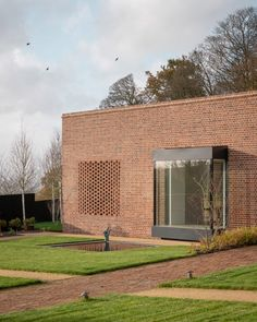 A linear red-brick wall obscures the textured interiors and art-filled courtyard hidden inside McLean Quinlan's low-rise Passivhaus home in Devon, UK.
